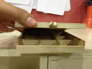 the same wooden box with a small button, affording a user to open it