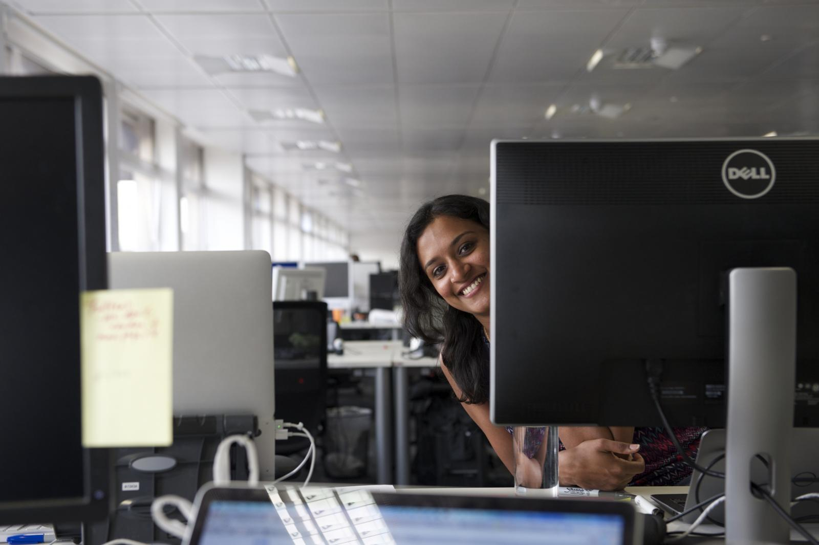 woman peeping out from behind her computer