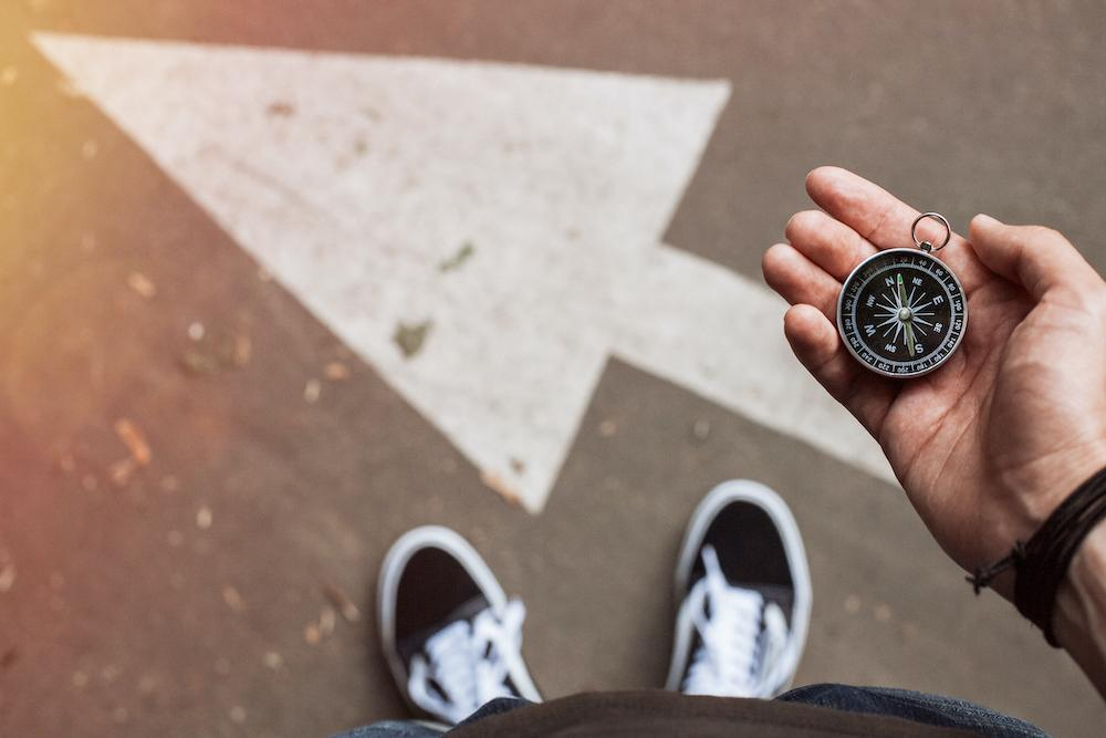 organizational growth requires the right questions and metrics to track | person holding a compass standing on a direction marker that is indicating left