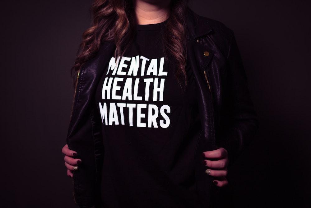 Photo by Matthew Ball on Unsplash Woman holding open shirt to reveal t shirt that says mental health matters