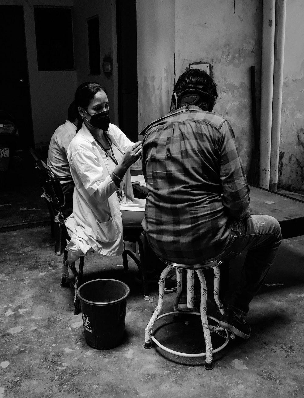 black and white picture of man sitting on a stool and a woman injecting him with a vaccine