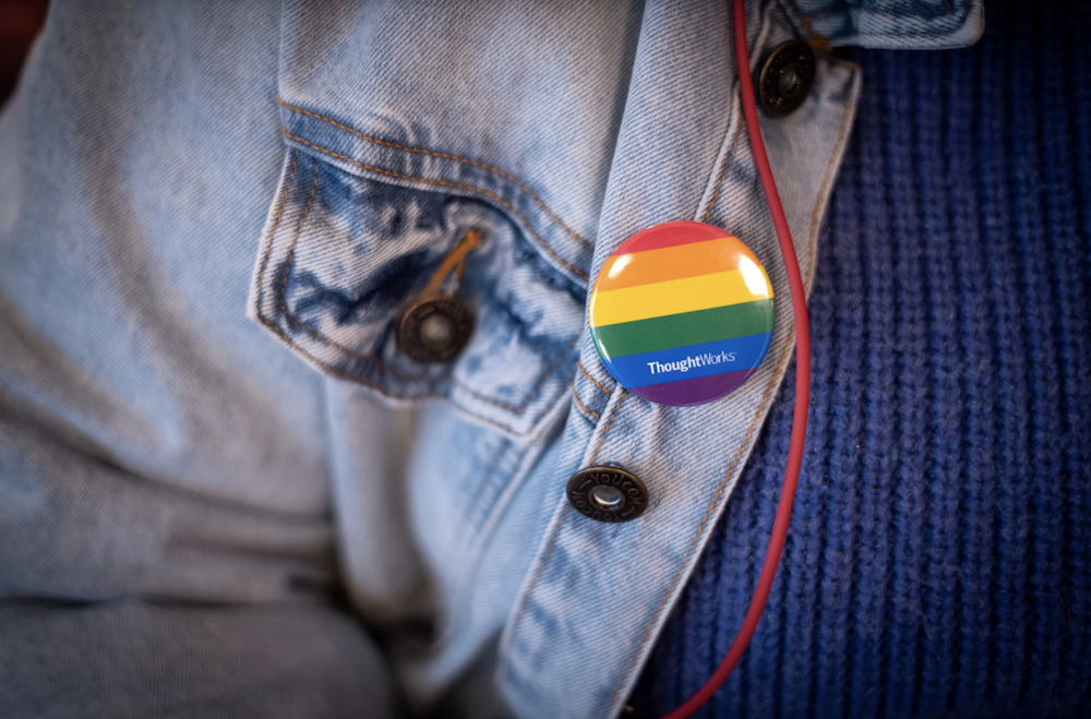pride flag pin on a blue jean jacket